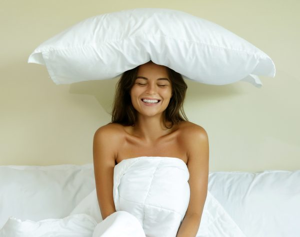Beautiful happy woman with a pillow on her head in the bedroom