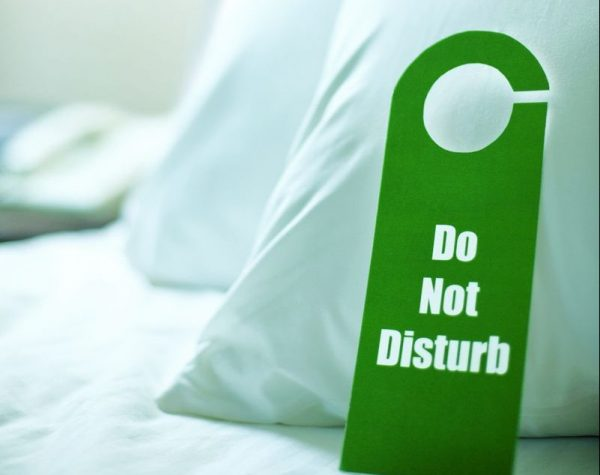 Do Not Disturb Sign on a Bed --- Image by © Tim Pannell/Corbis